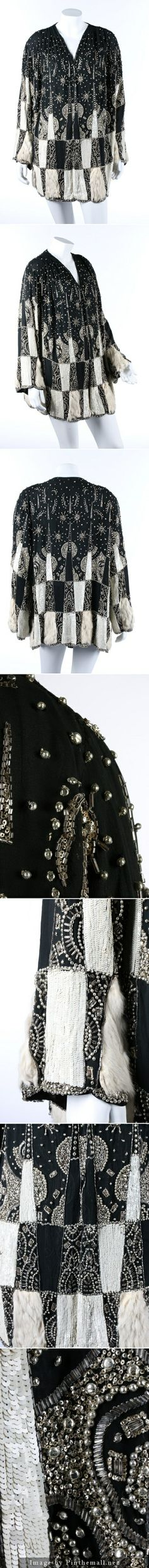 A beaded and sequined couture evening jacket, circa 1928. the black chiffon ground adorned with chequered bands in white sequins and fur, with stylised star and moon motifs in silver bugle beads, blister beads and tiny sequins. KTA