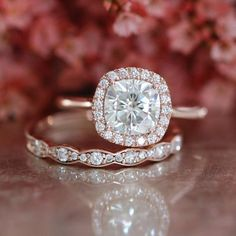 This bridal wedding ring set showcases a 7x7mm cushion cut Certified Charles & Colvard forever brilliant moissanite engagement ring set in a solid 14k rose gold halo diamond ring setting. To complete the gorgeous look, a gorgeous scalloped diamond wedding band is created to be paired with this stunning moissanite ring!