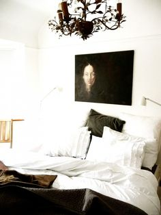 Fresh white sheets balance this bedroom's moody painting and chandelier
