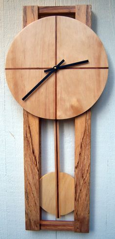 Modern Wall Clock. The face is reatta pine with magamba inlays. The base is made from the same African hardwood (  magamba) with a outstanding grain pattern. The pendulum is made to match the clock. The works are a Quartz pendulum movement.    There is no stain or coloring. The wood is its natural coloring. finely sanded with a satin lacquer.    The clock is approx 10 x 23 x 2