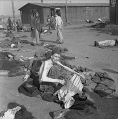 An emaciated inmate of Bergen-Belsen concentration camp is photographed by British liberating troops, sitting in the open amongst the dead and dying, delousing his clothing. In the background are Blocks 22 and 24 (Häftlingslager II). When the British and Canadians advanced on Bergen-Belsen in 1945, the German army negotiated a truce and exclusion zone around the camp to prevent the spread of typhus, which was widespread throughout the camp and killed thousands of inmates. Bergen-Belsen…