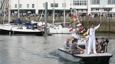 Torchbearer Luke Jones carries the Olympic Flame on a boat during the Torch Relay through St Peter Port.
