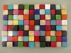"""This 18"""" x 12"""" piece consists of 2"""" x 2"""" slices of wood that have been cut to various thicknesses to provide depth and texture. The slices have been hand painted in shades of purple, yellow, teal, green, burnt orange, and brown, attached to 3/4"""" plywood, then varnished with tinted polyurethane to bring out the detail of the grain and add a slightly aged finish over the modern colors.  Every effort has been made to highlight the unique qualities of each slice, including cracks, knots, and…"""