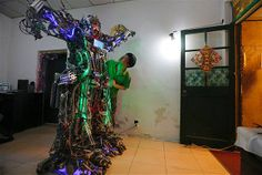 """Chinese inventor Tao Xiangli checks out his homemade humanoid robot during a demonstration at his house in Beijing, China. The self-taught Chinese inventor built the robot, named """"The King of Innovation,"""" out of scrap metal and electronic wires that he bought from a second-hand market..."""