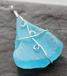 This is a beautiful sea glass pendant. This is made a piece of turquoise sea glass. The pendant is wrapped with square, silver artistic wire.    This pendant measures 2.25 tall. Slide onto a chain and you are ready to go. Back to my shop: akkricket.etsy.com