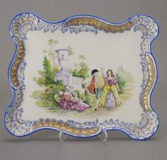 "Meissen Pictorial Porcelain Tray. The cartouche form with a gilt and royal blue feather and rocaille molded serpentine dish rim, elaborate corner shell medallions, center painted with a parkland vignette of a strolling courting couple, a seated mother and daughter, signed W. Duda, marked on base with cobalt blue crossed swords, paint ""5."" incised ""720.18"". Dimensions 14 1/2 x 18 inches (37 x 45.5 cm)"