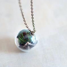 Un plumage de paon réel dans beau vert irisé. Ce collier est titulaire de trois plumes de paon de Paré minuscules à lintérieur de lOrbe de verre.