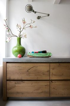 Kitchen: Jielde lamp on wall, concrete counter top and floor, old wood, white painted walls: