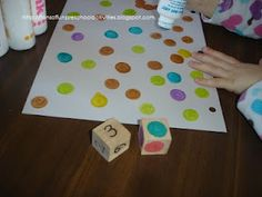 What a fun game! Make two dice: one with numbers, and one with colours. Roll the dice, then use dot stamps to make that number of dots in that colour on your paper.