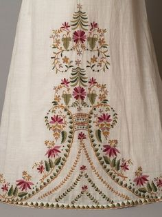 Dress  Place of origin: England, Great Britain  Date: 1812-1815  Museum number: T.29-1936 Techniques. Embroidering Artist: unknown (production) Materials: Muslin embroidered in wool   Girls dress of white muslin embroidered from the hem with a floral design in coloured wools. The dress has a high-waisted bodice, vertically-gathered puffed sleeves and a trained skirt.  Trouve a collections.vam.ac.uk