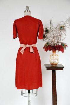 Vintage 1930s dress in a rich and lovely red crepe, a deep crimson shade with a bit of luster. The material is unusual, and I believe it is celanese or a celenese/rayon blend. A contrasting ivory bodice peeks through the scalloped bodice, giving the appearance of a jacket over a blouse. Tiny white buttons accent the scallops. The sleeves are puffed and darted. The waist is not very fitted but has belt loops - its intended to be worn with a sash.* A single inset pleat at the front gives t...