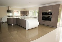 Contemporary curved kitchen island design.  This spacious kitchen includes a breakfast bar on the island as well as bespoke continuous curve formation for an elegant, flowing look.