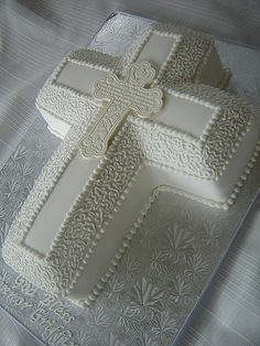 First Communion cake for a boy.  The cake is a combination of the Wilton cross pan and a 9x13 that I cut and pieced together to add more height.  It is covered in fondant with RI details.  The cross is made from white candy melts.