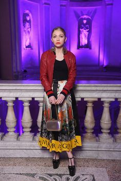 Tavi Gevinson in a pleated skirt with black velvet ribbon, leather bomber, platform high heels and leather clutch.