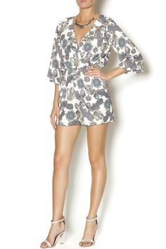 """Paisley printed romper with a plunging neckline and cross front. This romper features 3/4 length bell sleeves and elastic waistband. The bottom of this shorts are 15"""" long. Wear with knee high gladiator sandals and a fringe cross body bag."""