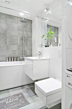 Badrum med tvättmaskin, torktumlare, vägghängd toalett och extra djupt badkar.