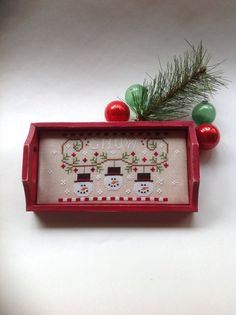 I have taken a sweet little snowman ornament by Country Cottage Needleworks and mounted it in a little wooden tray. This piece is stitched on a natural color linen with overdyed threads. It measures approx. 4 x 8 I have painted the tray a country red and distressed it a bit and then waxed it. This would make a fun little stitching tray for the holidays or a great gift for that special someone! Who doesnt love a snowman! Thank you for looking! Please feel free to message me if you have any…