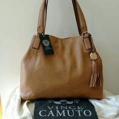 "NEW SALE Vince Camuto Leather Alesi Shoulder Bag Experience the quality and sophistication of genuine leather handbags from Vince Camuto. The Alesi shoulder bag is the perfect bag for an afternoon of shopping or evening out with friends.  Leather shoulder bag Flat handles with 8"" drop Removable tassel and gold logo embossed pendant Fabric lining with zip pocket and two slip pockets Dimensions 15"" x 4 1/2 "" x 11"" Vince Camuto Bags Shoulder Bags"