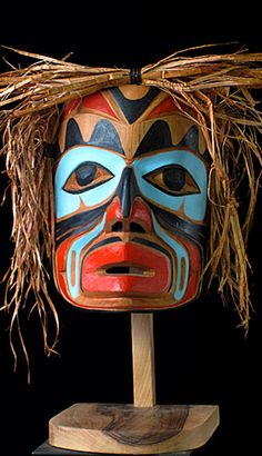Speaker Mask  NWC, Canada  7 1/2 inches, red cedar, paint, straw  Beautifully carved and painted by First Nation artist Peter Wayne. It is  traveler size-- not full size or the very small companion size.   The speaker (Alkw) was a hereditary official who acted as spokesman for the chief on all public and ceremonial occasions. He had a badge of office,