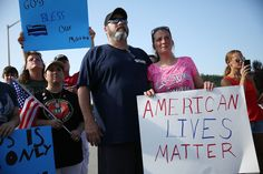 CHATTANOOGA, TN - JULY 19:  Ron Fahy and Misty Fahy hold a sign that reads,' American Lives Matter', as they attend a prayer service near the Armed Forces Career Center/National Guard Recruitment Office which had been shot up on July 19, 2015 in Chattanooga, Tennessee. . The gunman Mohammod Youssuf Abdulazeez, 24, opened fire on the military recruiting station at the strip mall on July 16th and then drove more than seven miles away to an operational support center operated by the U.S. Navy…