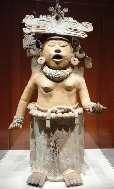 The famous Aztec statue of Xochipilli, the god of art, beauty, and games, in a trance and moaning under the influence of the psychotropic flowers that ornament his body.