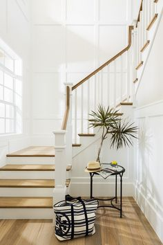 A cottage foyer boasts a white staircase with blond treads and banister next to a small nook filled with a round iron table with glass top. White Staircase, House Staircase, Staircase Remodel, Modern Staircase, Staircase Design, Staircase Ideas, Staircase Pictures, Spiral Staircases, Design Entrée