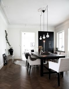Black and white home of Daniella Witte    lighting over kitchen counter! wood floors - chevron