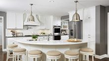 White Kitchen, curved kitchen island, restoration hardware, island lights, double oven, stainless steel, appliances, counter stools, white tile, subway tile, dark wood floor, curved kitchen hood, wood hood, large industrial lights, open kitchen, family kitchen, white counter top, marble counters
