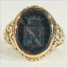 This antique Victorian Intaglio ring was handcrafted in 18k gold in c. 1860. The oval shaped bloodstone presents a seal that pictures a shield below a coronet.