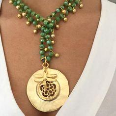 Collar largo de cristal de roca adornado con medallón y libélula pequeña todo bañado en oro mate y adornada con bolitas pequeñas también bañadas en oro mate. La