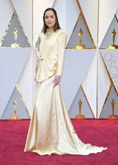 Dakota Johnson saved her most prize-worthy gown for the Oscars red carpet. Dakota was a statuesque vision in this solid gold perfection by Gucci.