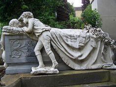 Monumental Cemetery of Bonaria, Italy...Cemetery with many huge and expensive monuments among cypress trees.  This one is the wife of a wealthy man; made of several monuments...this is her son mourning her and covering her with blanket.  It is astounding.