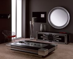 round mirror, sitting case and coffee table which is also cd and dvd storage for an art deco home living  silver and black