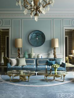 In the living room of a Paris apartment, which was designed by Jean-Louis Deniot, a sofa by Collection Pierre is upholstered in a Brochier fabric trimmed with ribbons by Samuel & Sons; lamps by Paul Evans flank a glass wall sculpture by Christophe Gaignon, the cocktail tables are custom designs, and the walls are painted in Paint Library's Eucalyptus.