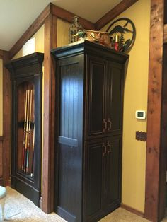 Left over bargain cabinets, Craigslist shelf turned pool stick cabinet. Shhhhh it's really a secret door hiding furnace