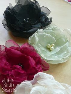 DIY chiffon, tulle, satin flowers  *Your desired fabric(s)--we used a combination of organza, tulle, and satin  *Beads or buttons for the center  *Invisible (clear) thread and a needle  *Scissors  *Candle and matches  Cut material in flower shape, cinge edges with candle.  Layer 4 flowers and sew bead or button in center.