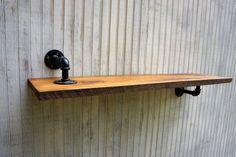 Reclaimed wood shelf with reversed pipe supports. By Loft Essentials