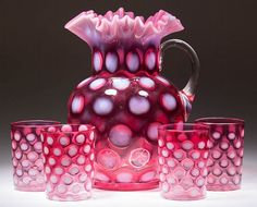 COINSPOT FIVE-PIECE WATER SET, cranberry opalescent, comprising a water pitcher with applied handle and four tumblers with three having factory polished rims. Jefferson Glass Co. and Fenton Art Glass. Circa 1910. 3 5/8' to 9 3/4' / SOLD $184