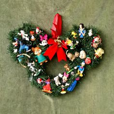 A wreath in the shape of Mickey decorated with original disney figurines just perfect for nursery room's decor