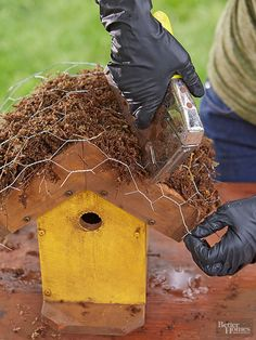 Staple poultry wire on top to hold the sphagnum moss in place. Then trim the wire back to the edges of the roof with scissors.
