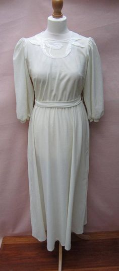 1970s Binett wedding maxi dress Beautiful clean lines! Cream/ivory fabric Illusion neckline with lace flower applique Full a-line skirt 1/2 puff sleeves Horizontal darts at bust Label: Binett Denmark Condition: very good vintage condition Closure: zipper on back, belt of