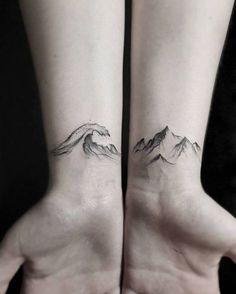 Matching wave and mountain tattoos on the inner wrist.