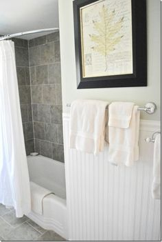 pretty updated bathroom with gray tile and shower and beadboard