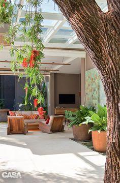 Casa grande com jardim em São Paulo tem clima carioca. As árvores existentes no terreno foram mantidas, a exemplo deste pau-formiga, que dá flores vermelhas pendentes.