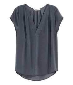 Short-sleeved V-neck blouse in satin with pleats on the shoulders and at the back of the neck, and a rounded hem that is slightly longer at the back.