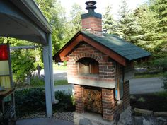 Outdoor Pizza Oven with a Gable Roof and fully enclosed Red Brick Housing. The backside is overlapping Copper Shingles. BrickWoodOvens.com