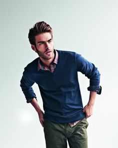 Jon Kortajarena's style for men: Olive green chinos, plaid shirt and blue pullover.