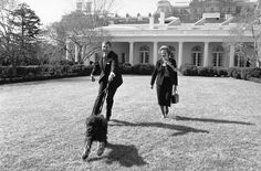 Thatcher joins US President Ronald Reagan (pulled along by his pet dog, Lucky) for a walk through the White House Rose Garden, on Feb. 20, 1985.AP