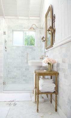 Gorgeous bathroom renovation with champagne brass, marble subway tile and a full length brass mirror from French Country Cottage