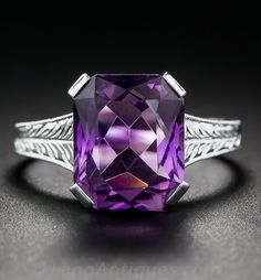 Art Deco Amethyst Ring,  A bright, royal purple, emerald-cut amethyst with a fancy faceting arrangement glistens solo from within a crisply hand engraved solitaire setting crafted in gleaming 18K white gold - circa 1930s. The all around engraving indicates that the ring has never been resized